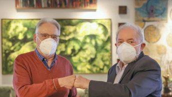FHC e Lula juntos, unindo os punhos fechados e olhando para a câmera. Ambos usam máscaras. Ao fundo, uma parede com diversas obras de arte. Foto: Ricardo Stuckert / Instituto Lula.