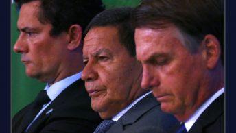 Foto de Sergio Moro, Hamilton Mourão e Jair Bolsonaro juntos, lado a lado, o três com semblantes sérios.