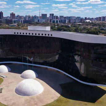 Foto ampla do prédio do TSE (Tribunal Superior Eleitoral), p´redio com fachada de vidros pretos e desenho côncavo. À frente do edifício, um jardim e três esculturas de formato circular.